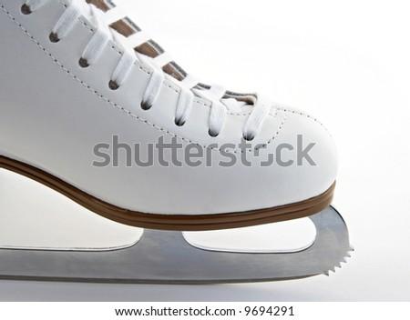 Toe and blade of a white elegant figure skate. - stock photo