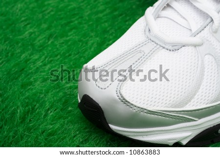 Toe of sneaker on grass – ready for workout - stock photo