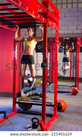 Toes to bar woman pull-ups 2 bars workout gym - stock photo