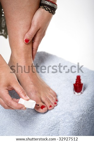 Toes with red nail polish. In beauty salon