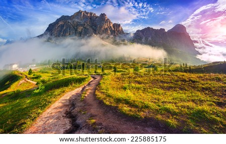 Tofane mountain range at sunny foggy morning. View from Falzarego pass. Dolomites mountains, Italy, Europe. - stock photo