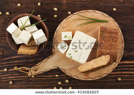 Tofu and tempeh background on brown wooden background. Culinary vegan eating.