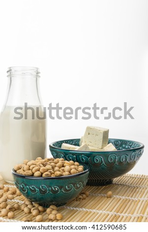Tofu cut into cubes with soybeans in bowl and soy milk,  on white background with copy-space - stock photo
