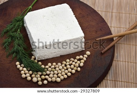 Tofu piece with soy beans on a wooden board. - stock photo