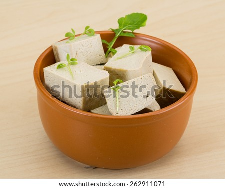 Tofu - soya cheese with herbs on the wood background - stock photo