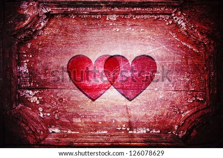 Together forever: two hearts inside an old wooden frame. Vivid red color with dark edges. Aged rough background. - stock photo