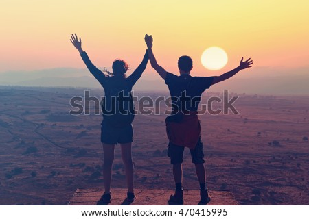 Together in wondering world. Young man and girl holding hands up, standing on the mountain top against sunset. People, love, nature and travel concept .Toned colors. Old style photo