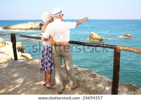 together into the future - senior couple in love gazing into space - stock photo
