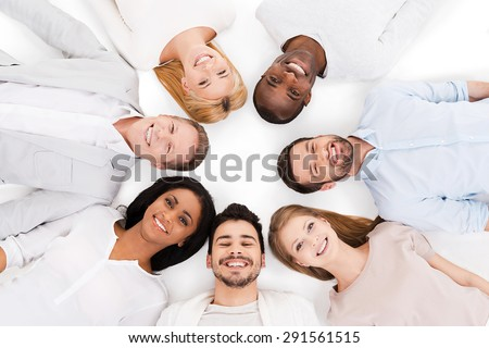 Together we are stronger. Top view of cheerful group of multi-ethnic people laying on their backs and smiling while standing isolated on white - stock photo