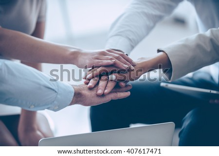 Together we can do everything! Close-up part of top view of group of four young people holding hands and showing their unity while sitting at office  - stock photo