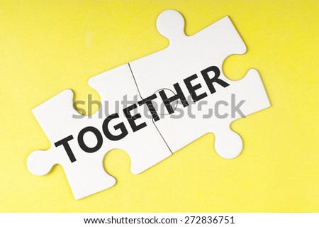Together  word on two pieces of jigsaw puzzle - stock photo