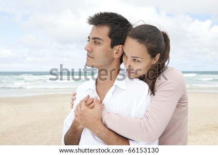 togetherness and trust: hispanic couple bonding on beach - stock photo