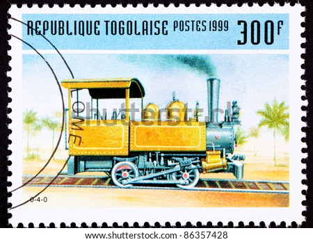 TOGO - CIRCA 1999: A stamp printed in Togo shows a small and early design railroad steam engine locomotive, made by H.K. Porter, circa 1999. - stock photo