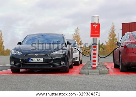 TOIJALA, FINLAND - OCTOBER 17, 2015: Three Tesla Model S cars are plugged in at Tesla Supercharger station. Supercharging is free for the life of Model S. - stock photo