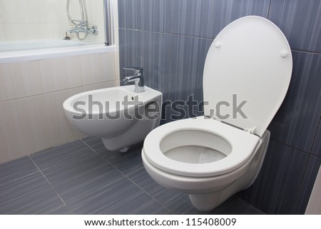 toilet and bidet in the gray bathroom - stock photo