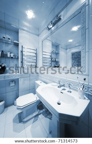 Toilet bowl and sink in a modern bathroom - stock photo