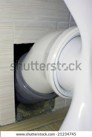 Toilet bowl connection to the water drain with use of polyvinyl-chloride pipes at repair in a public toilet
