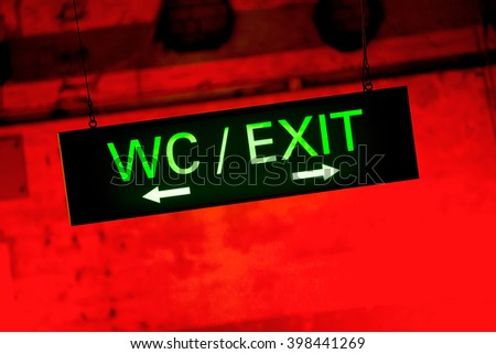 toilet & exit signs hanging at a red wall - stock photo