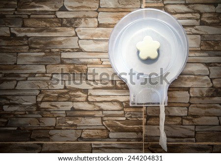 Toilet paper holder mounted on the ceramic tiled bathroom wall - stock photo
