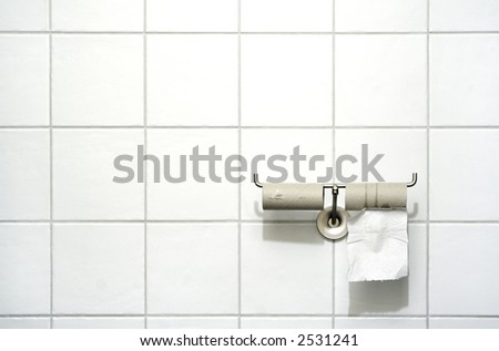 Toilet paper holder with two rolls, one empty, one with a single sheet - stock photo