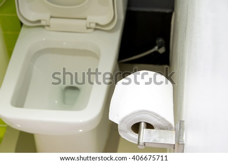 toilet paper on the wall in the bathroom - stock photo