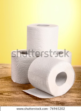 Toilet paper on yellow background - stock photo