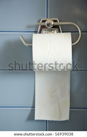toilet paper roll hanging in bathroom close up with blue ceramic - stock photo