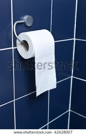 Toilet paper roll hanging with blue tiles - stock photo