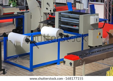 Toilet paper rolls making machine in factory - stock photo