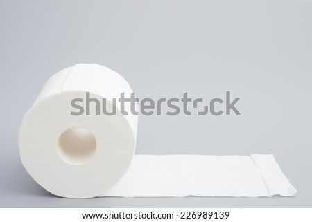 toilet roll on grey background - stock photo
