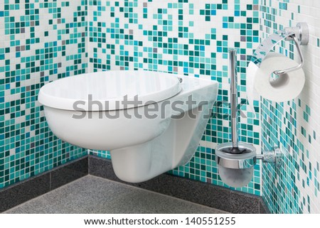 Toilet seat and paper in clean bathroom - stock photo
