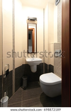 Toilet seat and sink in small tidy bathroom