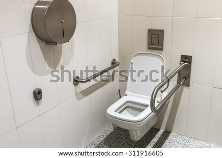 toilet with handrails for the disabled. Focus on the lid of the toilet  - stock photo