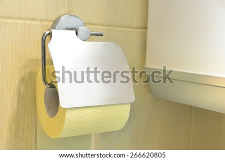 Toilet yellow paper and toilet paper holder.