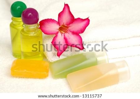 Toiletries and flower on white towel - stock photo