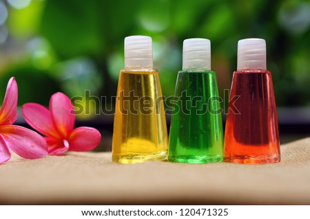 Toiletries and plumeria flowers with green background - stock photo