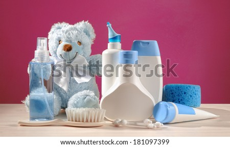 toiletries baby, blue items and pink background - stock photo