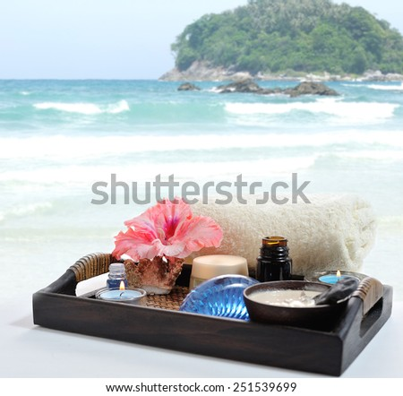 toiletries with flower and candles on a tray near the sea - stock photo