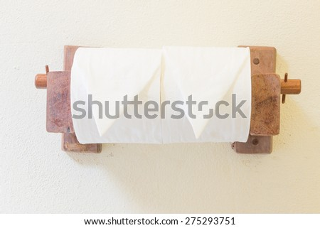 Toilets Paper Rolls hang on concrete background - stock photo