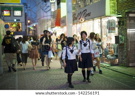 TOKYO - AUGUST 5 : People, mostly youngsters, walk through Takeshita Dori near Harajuku train station on August 5, 2012. Takeshita Dori is considered a birthplace of Japan's fashion trends. - stock photo