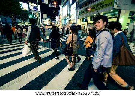 TOKYO - CIRCA APRIL 2013: people on the crosswalk in the evening in Shinjuku district of Tokyo, Japan circa April 2013.  - stock photo