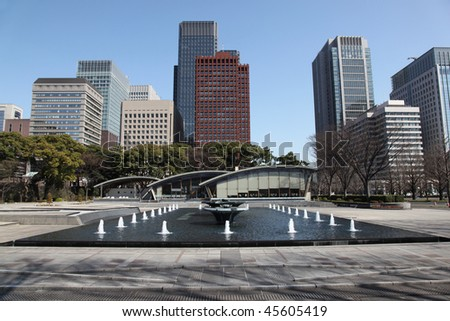 Tokyo cityscape with decorative fountain in foreground.