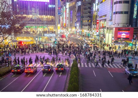TOKYO - DECEMBER 10: Pedestrians cross at Shibuya Crossing on December 10, 2013 in Tokyo, Japan. The crosswalk is one of the world's most famous implementations of a scramble crosswalk. - stock photo