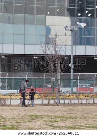 Tokyo - February 7, 2015: Father and young son flying a kite in the pedestrian area of the city in early spring February 7, 2015, Tokyo, Japan - stock photo