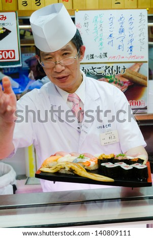 TOKYO - JANUARY 17: Japanese cook prepares sushi in a restaurant on January 17, 2013 in Tokyo. Sushi is the world famous gem of Japanese cooking.  - stock photo
