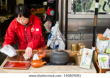 TOKYO- January 17: Japanese woman preparing tea at Tokyo street stall on January 17, 2013 in Tokyo. Green tea is very renown drink in Japan.