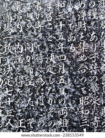TOKYO, JAPAN - APRIL 21, 2012: A portion of the writing in Kanji characters on a granite stone tablet in the historic Benzaiten Temple in Ueno Park in Tokyo. - stock photo