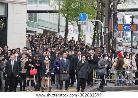 Tokyo, Japan - April 12, 2015: Hundreds of People are waiting for crossing the street at Shinjuku, a major commercial and administrative center, housing the busiest railway station in the world. - stock photo