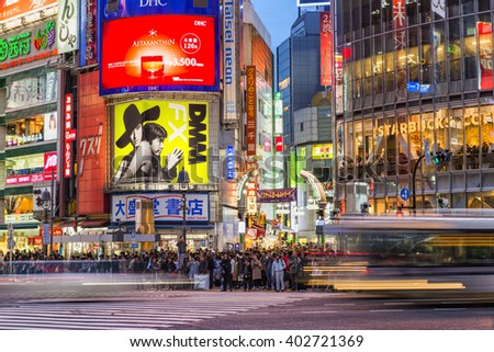 TOKYO, JAPAN - APRIL 04, 2016: Pedestrians walk at Shibuya Crossing during the holiday season. The scramble crosswalk is one of the largest in the world. - stock photo