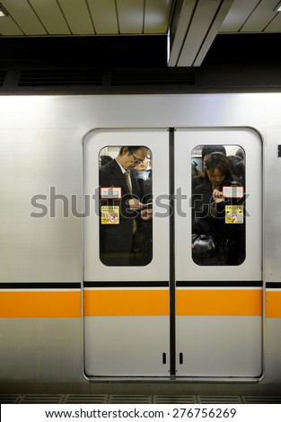 TOKYO, JAPAN - APRIL 8 : People in subway train in rush hour taken April 8, 2013. People in Tokyo use subway underground as main transportation.  - stock photo
